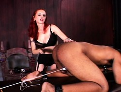 Muscled servant is chained, spanked, and probed anally wits a flame-haired dominatrix