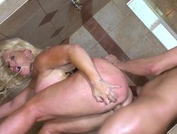 A blonde milf is receiving some cock in her pussy in the bathroom