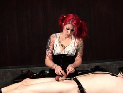 Dominatrix with scorching hair restrains her bound slave's cock with the co-conspirator of bilge water with chains