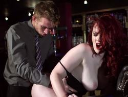 A redhead around large tits is handling a cock in a bar